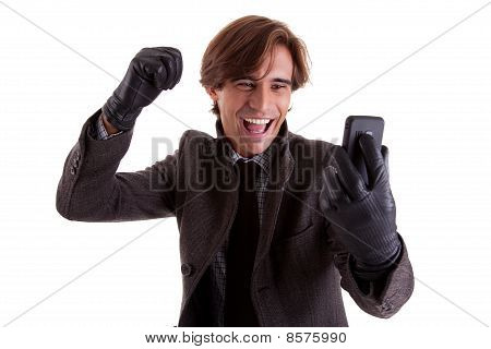 Portrait Of A Young Happy Businessman Looking To The Phone, In Autumn/winter Clothes, Isolated On Wh