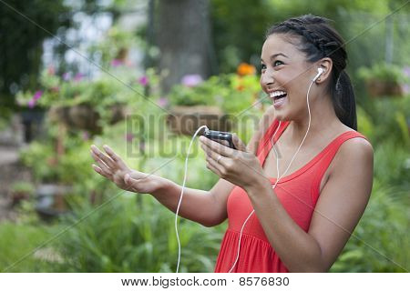 Cute Young Woman Dancing to Music Outdoors