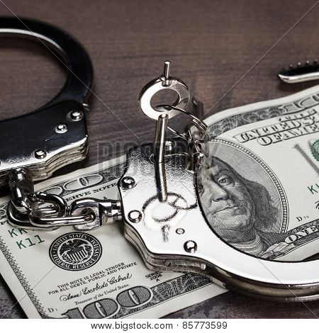 handcuffs and one hundred dollars on the table