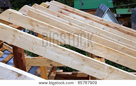 Installation of wooden beams at construction the roof truss system of the frame house poster