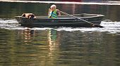 Young boy practices rowing the boat while his dog patiently goes for a ride. poster