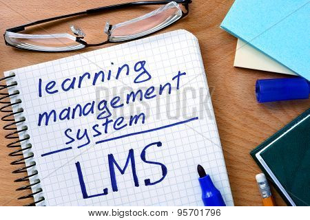 Note with words learning management system LMS on a wooden background.
