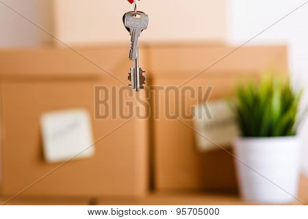 Female Hand Holding Keys Over Pile Of Brown Cardboard Boxes