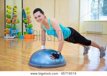 young beautiful slim woman doing push ups with bosu ball in gym poster