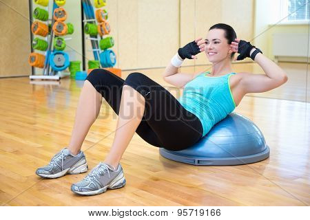 woman doing exercises for abdominal muscles on bosu ball in gym poster