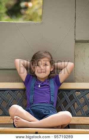 Little Girl On Outside Bench