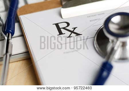 Prescription Form Clipped To Pad Lying On Table With Keyboard And Stethoscope
