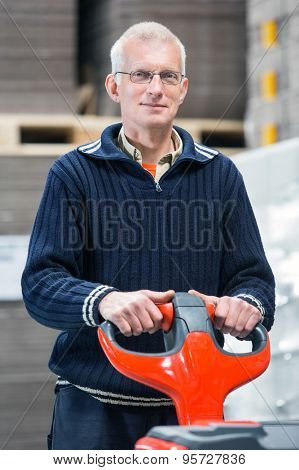 Portrait of confident male worker holding handtruck while standing at warehouse
