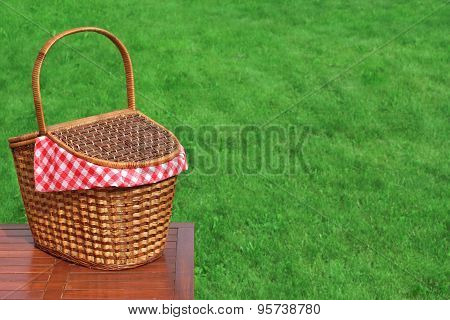 Picnic Basket On The Outdoor Rustic Wood Table Close-up