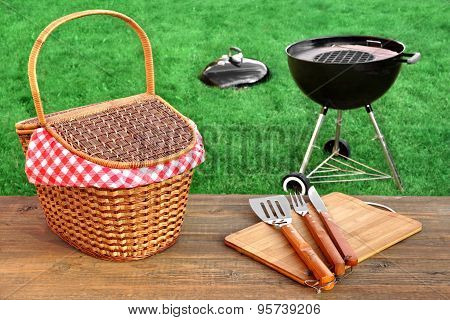 Outdoor Picnic Or BBQ Grill Party Scene At Summertime. Picnic Table With Hamper And Grill Tools Close-up Barbecue Appliance On The Fresh Lawn In The Background. poster