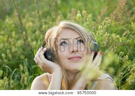 Beautiful Girl Listens To Music In The Meadow