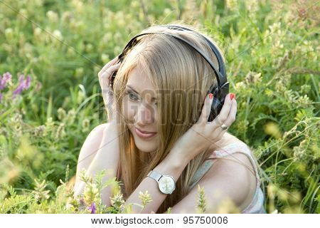 Girl With Headphones On The Grass