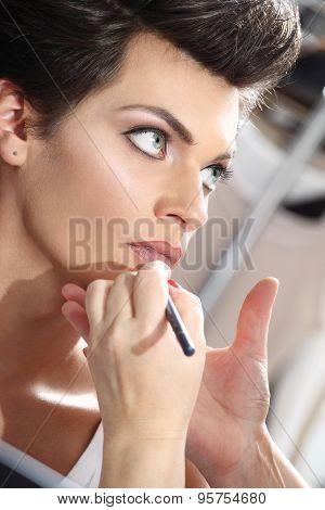 beautiful model having lip liner applied by makeup artist