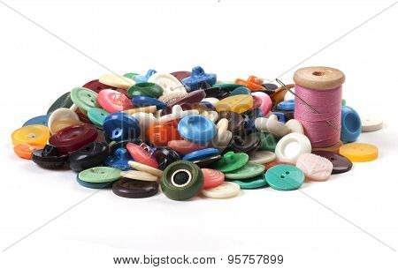 Pile Of Old Colored Buttons With Thread And Needle On White Background