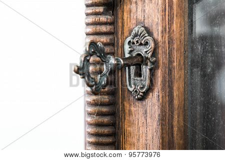 Vintage keyhole with key on vintage wooden cabinet with white background