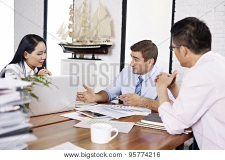asian and caucasian business executives reviewing and discussing business performance in office of a multinational company. poster