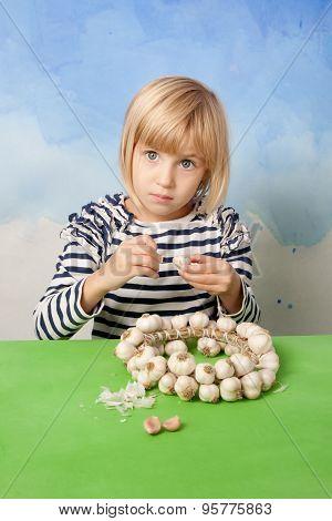 Little pretty girl peeling garlic from a wattled wreath poster