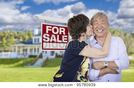 Attractive Affectionate Senior Chinese Couple In Front of Beautiful House and For Sale Real Estate Sign.