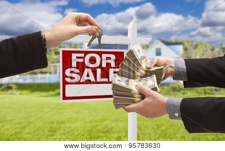 Man Handing Woman Thousands of Dollars For Keys in Front of House and For Sale Real Estate Sign.