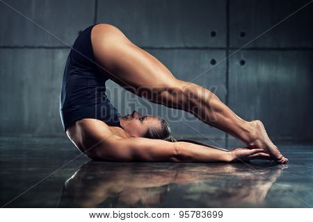 Strong woman bodybuilder stretching upside down in urban interior.