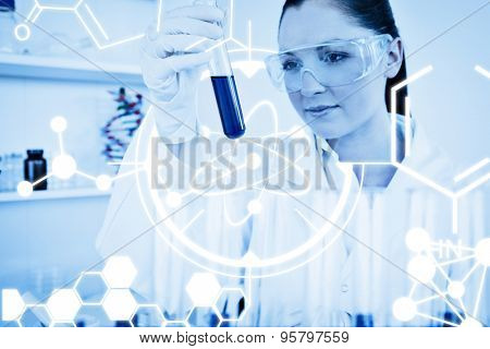 Science graphic against beautiful redhaired woman holding a test tube