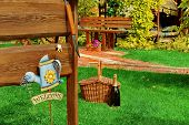 Outdoor Wooden Furniture Picnic Hamper Basket Champagne Wine Bottle BBQ Grill Tools Empty Wood Signboard Sign Garden Plants Trees In The Background. Backyard BBQ Grill Party Or Picnic Scene poster