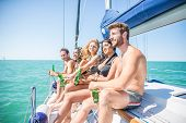 People on a yatch drinking beers while talking and laughing - Group of friends toasting drinks and having party on a sailing boat - Tourists on vacation poster