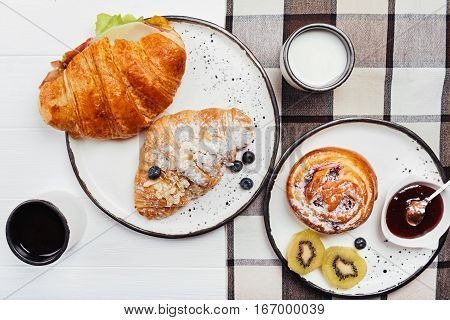 Gastronomic perfection. Homemade healthy breakfast consisting of different types of croissants and pastry arranged on neat while dishes which standing of white table covered with checked cloth