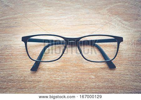 Clear Eyeglasses Glasses with Black Frame Fashion Vintage Style on Wood.