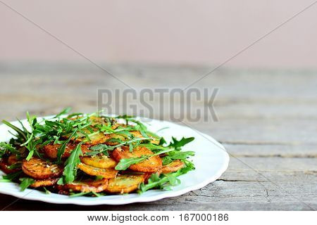 Crispy round potatoes with rucola on a white plate. Roasted potatoes with spices and fresh rucola recipe. Simple and delicious vegetable side dish. Wooden background with copy space for text