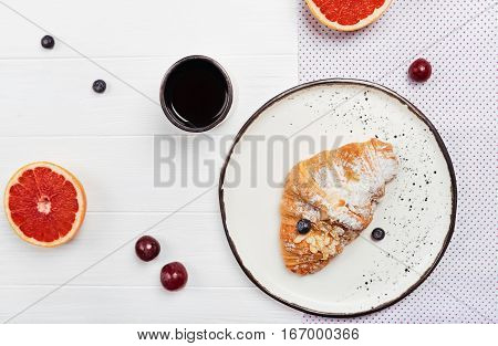 Quick meal for the start. Delicious freshly baked croissant with berries lying on white plate standing near cup of morning coffee surrounded by fruits and berries
