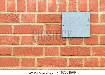 pattern created by cooked clay bricks get togheter to build a wall with a blue metal plaque