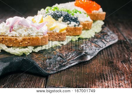 Sandwiches of bran bread with farmer cheese and various tops served on board