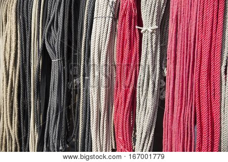 Gray white and red colored rope hanging on market for sale