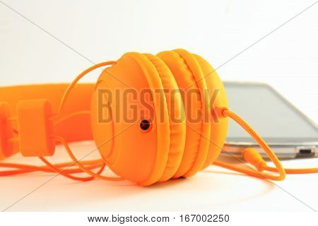 Mobile phone and headphones on orange light background