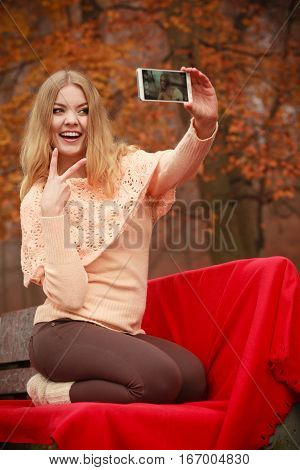 Photography people concept. Blonde young girl taking a selfie. Beautiful woman takes picture with mobile phone.