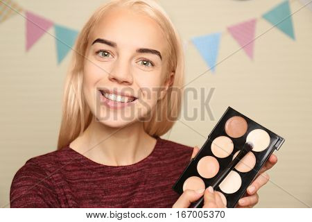 Beautiful young woman holding concealer tonal palette