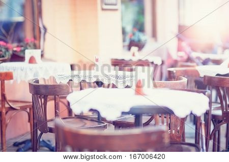 An outdoor cafe with vintage chairs tables white table cloths.