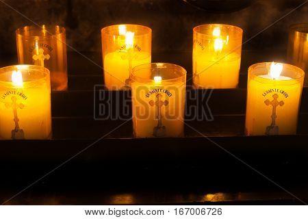 St.Guilhem Le Desert, France - September 30, 2016: Holy Cross prayer  candles burning in Abbey of Gellon and church in picturesque historic southern French village Saint Guilhem Le Desert