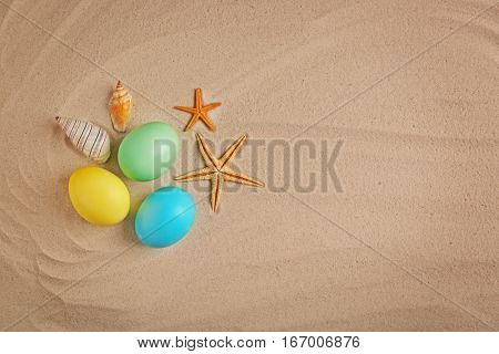 Easter eggs with shell, on sand background
