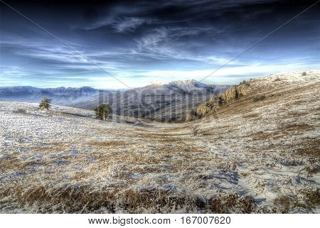 an open meadow in the mountains swept by snow, meadow covered with frost in the mountains, blue sky with clouds, the tip of the snow-covered mountains on the horizon