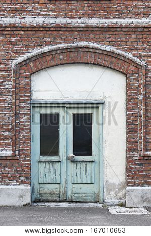 Antique brick facade with green doors. Old style warehouse entrance. Construction