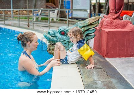 Young cheerful mother and todler son in a swimming pool. Holidays with family concept.