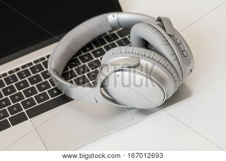 Wireless headphones and modern  laptop computer in one picture