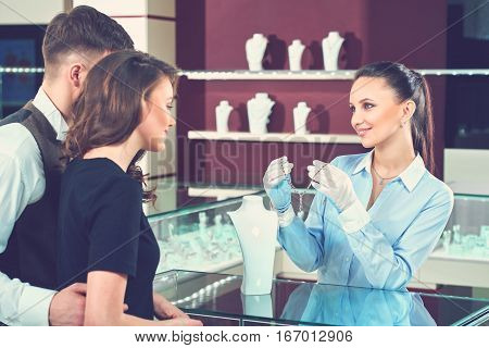 Couple of brunette woman and man looking and choosing at golden necklace at luxury jewelry store. Pretty smiling seller holding and showing beautiful necklace with blue stones for couple of buyers.