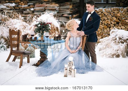 Winter wedding outdoor on snow and firewood background. Bride sits on a chair groom stands close by. Beside them is chair and table with goblets of wine and bouquet.