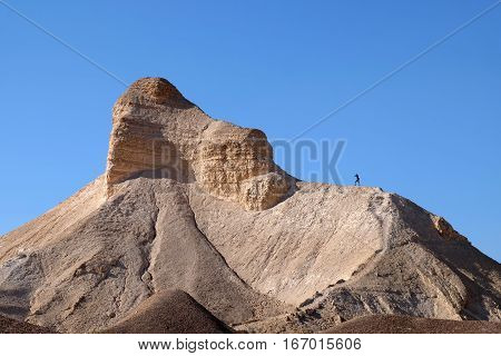 Female hiker standing on mountain ridge in Judea Desert Israel.