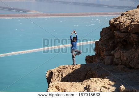 Female hiker standing on rock cliff above Dead Sea Judea mountains in Israel.