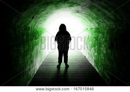 Silhouette of woman standing in front of light at end of green tunnel - dead end