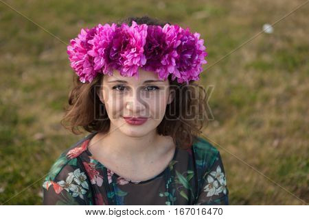 Beautiful curvy girl with a flower crown in the landscape